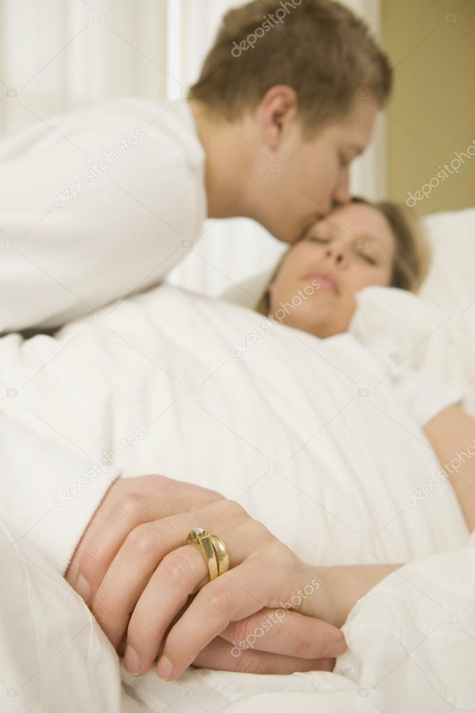 Loving Husband Caring For Sick Wife In Bed