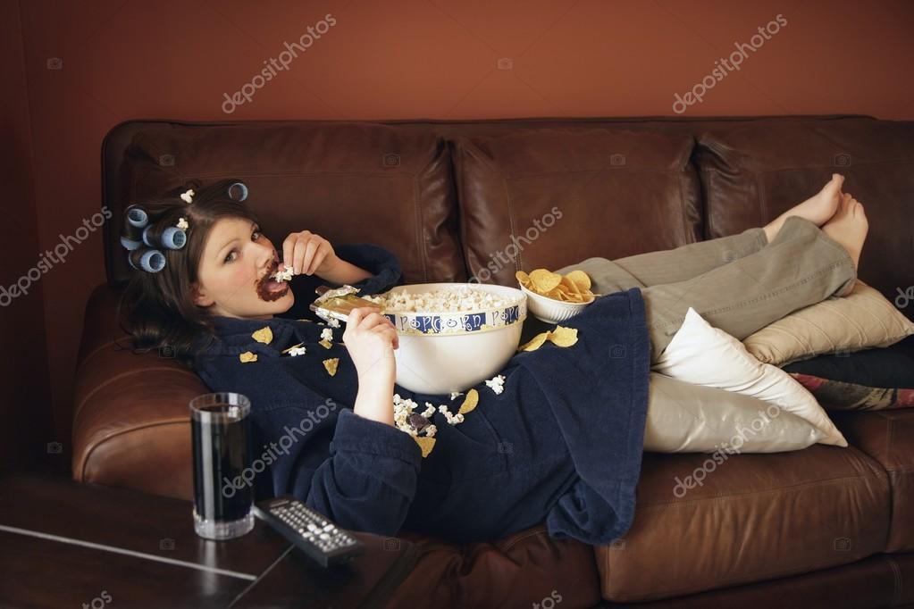 Ragazza sul divano mangiando popcorn foto stock - Chiavata sul divano ...
