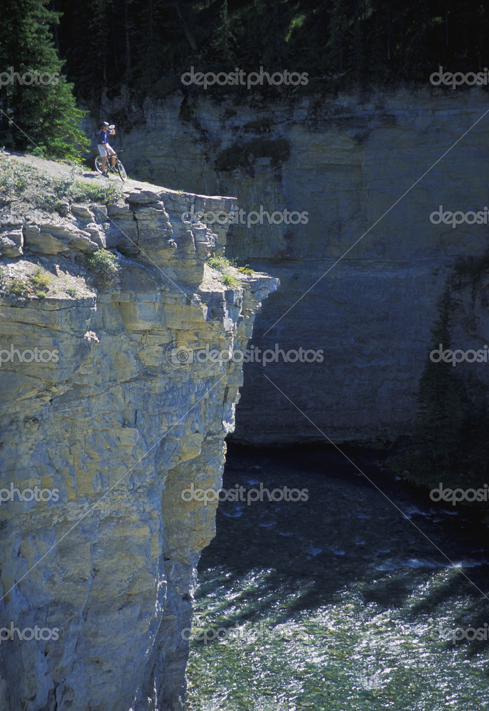 Cyclist Looking Over Cliff