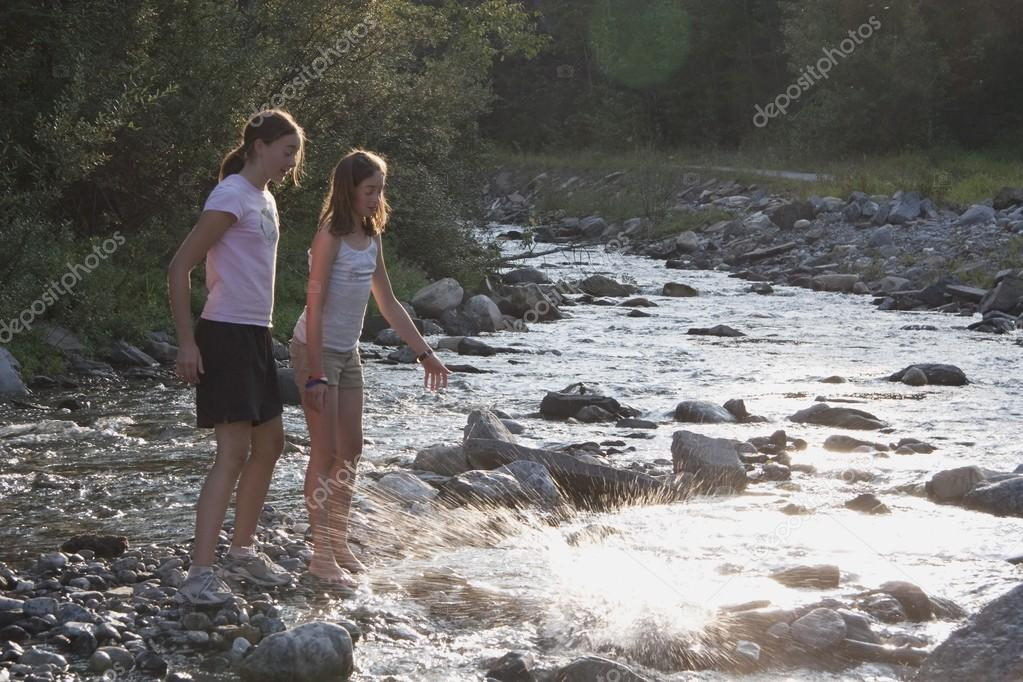Two Girls Throwing Rocks Into The River