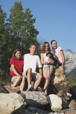 Family Sitting On The Rocks In The Mountains With Their Dog