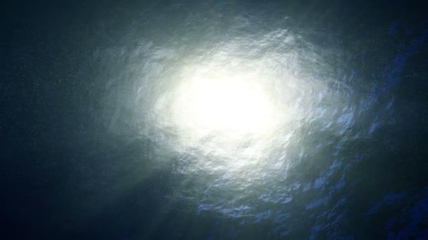 Sun shining trough slow motion looped ocean surface