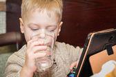 Chlapec pitné vody s tabletovým počítačem