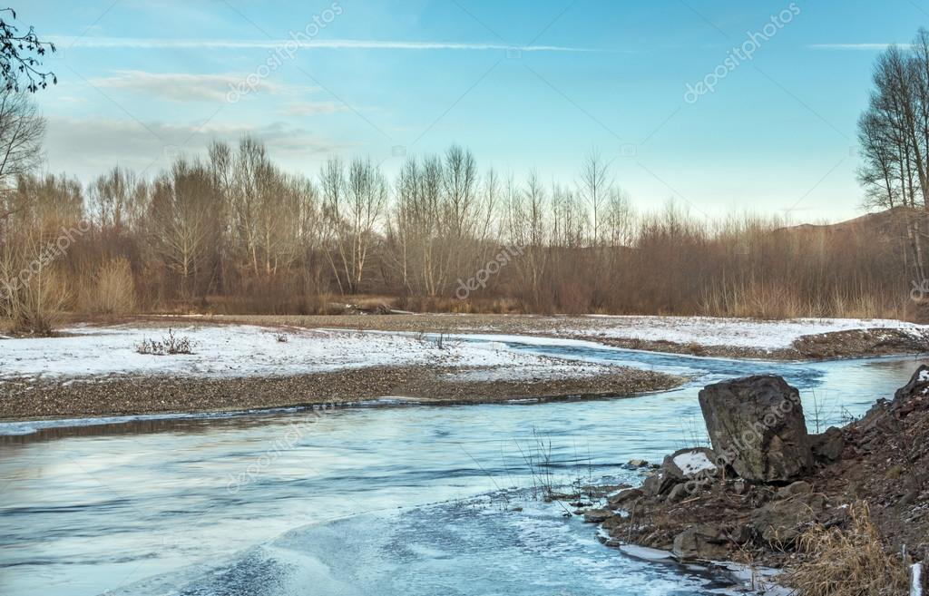 autumn landscape of river and trees without leaves blue sky and clouds on a sunny day