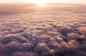 mraky při západu slunce z okna letadla