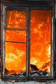 Plameny požáru v domě okna