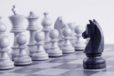 Black knight facing white chess pieces