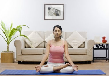 Woman meditating in a living room