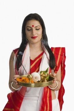Woman in a Bengali sari holding puja thali