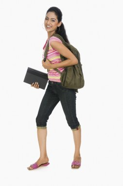 Student carrying a bag and books
