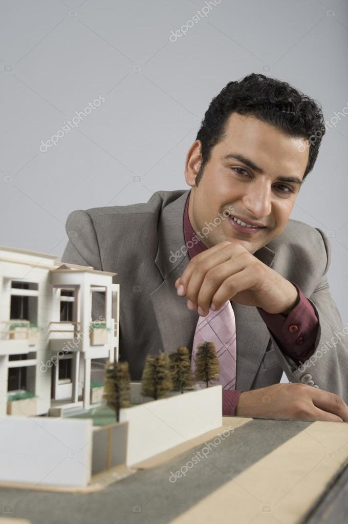 Businessman with a model home in an office