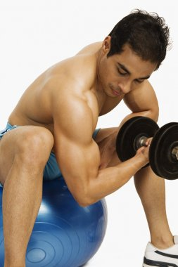 Man exercising with dumbbell on a fitness ball
