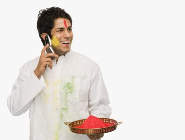 Man holding Holi colors and talking on a mobile phone stock vector