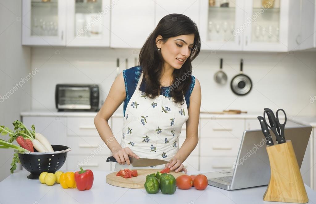 Mujer cocinando con la receta en un ordenador port til for Cocinando con sergio en la1