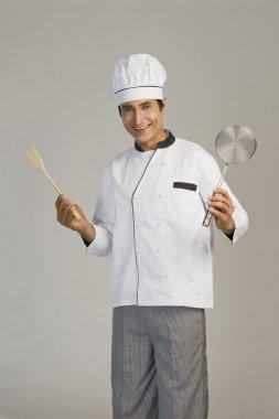 Chef holding a sieve and a wooden spoon