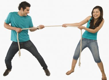 Young couple playing tug of war