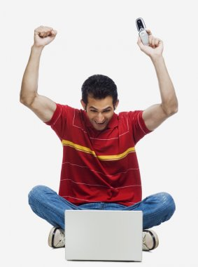 Man cheering in front of a laptop