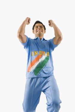Cricket bowler celebrating with his arms raised