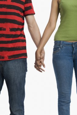 Mid section view of a couple holding hands