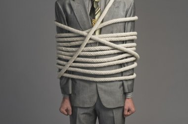Businessman tied up with ropes