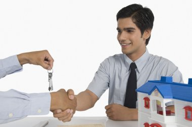 Real estate agent offering keys to a customer
