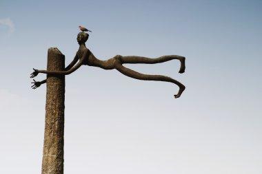 Bird perching on a sculpture