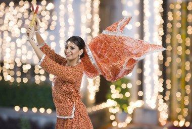 Woman performing Dandiya Raas at Navratri