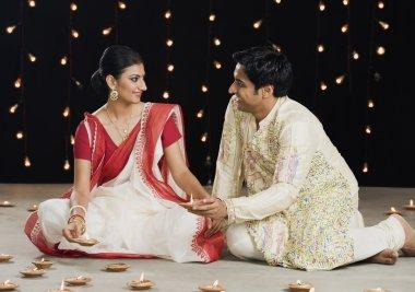 Bengali couple lighting oil lamps