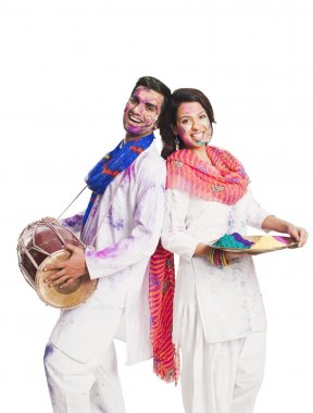 Couple celebrating Holi with colors and a drum stock vector