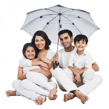 Family sitting under an umbrella
