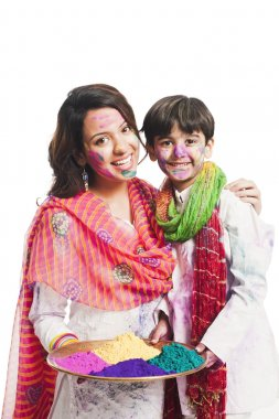 Woman celebrating Holi festival with her son stock vector