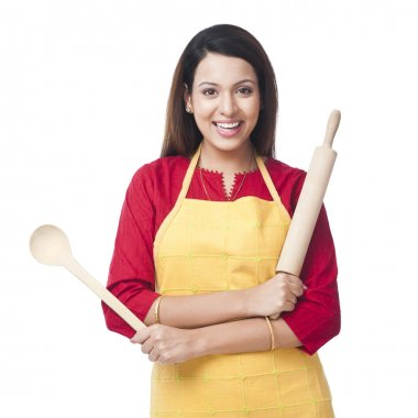 Woman holding a rolling pin and ladle