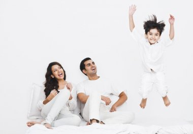 Boy jumping on the bed with his parents