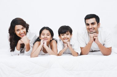 Happy family smiling on the bed