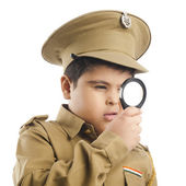 Photo Close-up of a boy dressed as a police uniform looking through a magnifying glass