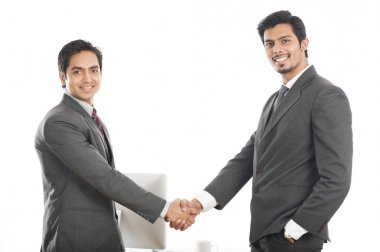 Two smiling businessmen shaking hands