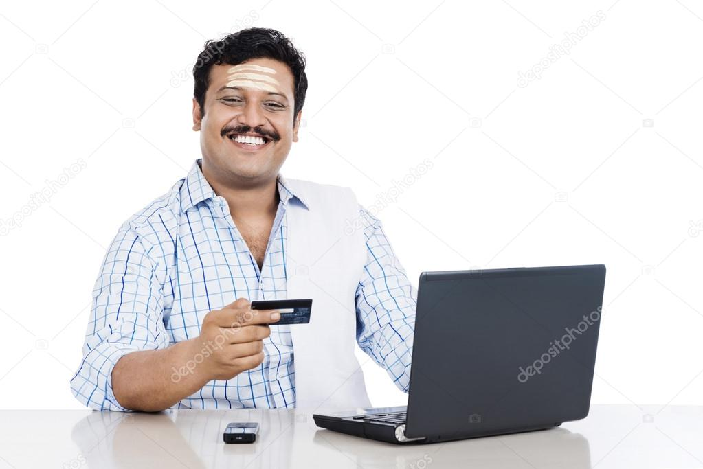 South indian man doing online shopping with a credit card stock south indian man doing online shopping with a credit card stock photo reheart Images