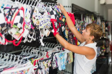 Beautiful smiling woman shopping in retail store,woman buys in the store swimsuit