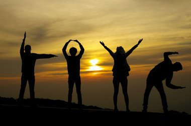 Love silhouette by four people on sunrise background