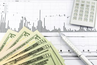 Stock graph report with calculator, pen and usd money for busine