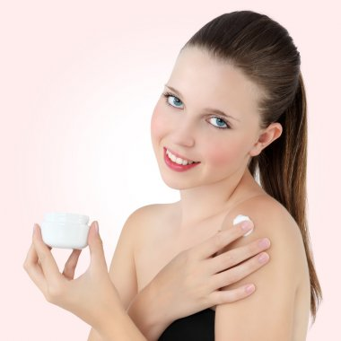 Smiling woman with cream lotion on background pink