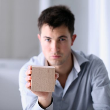 Man showing a wooden cube