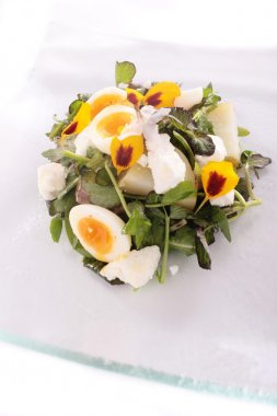 Salad with poached quails eggs, flowers