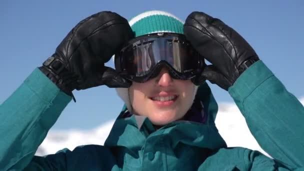 snowboardista dívka staví na lyžařské brýle