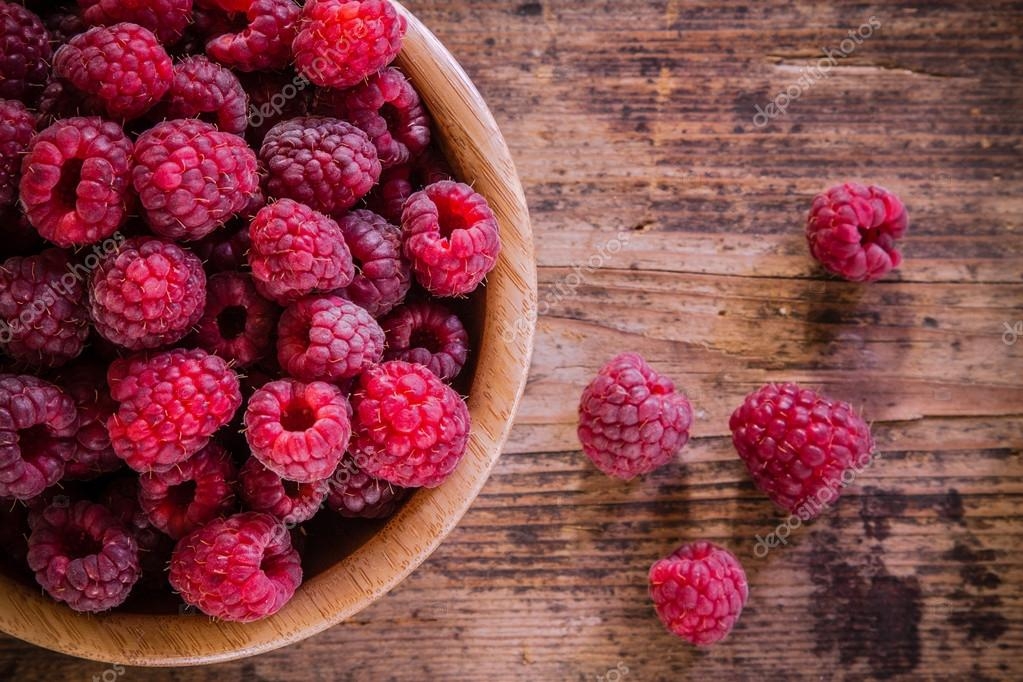 organic raspberries in a bowl on wooden background