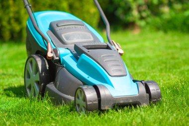 blue lawn mower on green gras