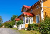Photo Wooden yellow house with red roof in Scandinavian style