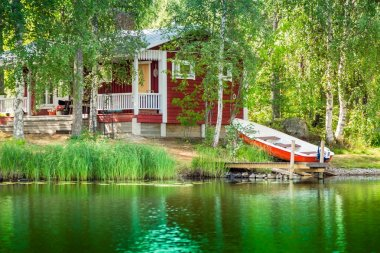 Old red Finnish summer cottage at a lake