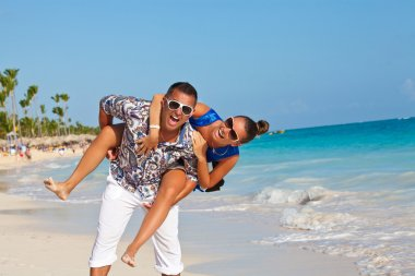 Couple having beach fun piggybacking
