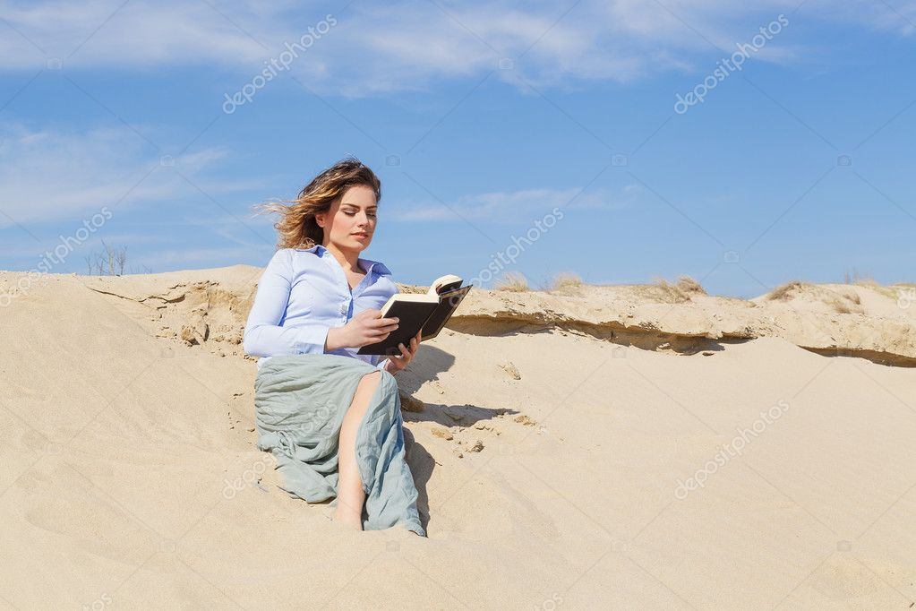Attractive young blonde woman reading a book on the beach